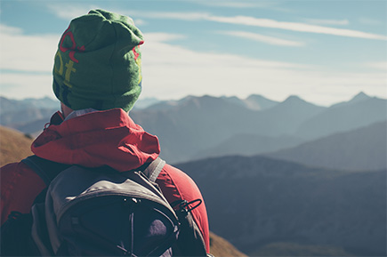 man with backpack looking out at mountains